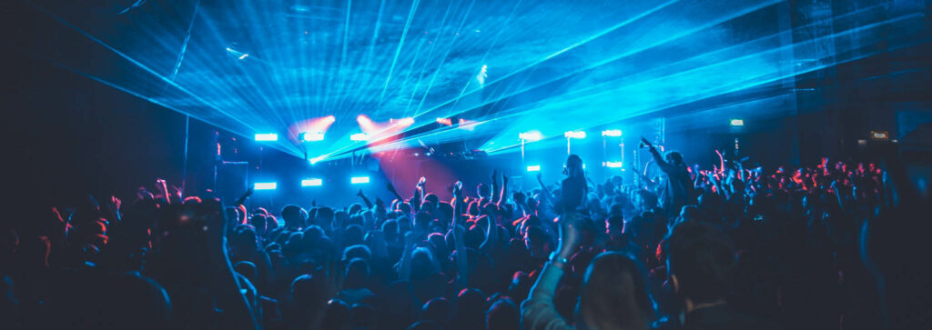 Picture of a music event with a big crowd and blue lights
